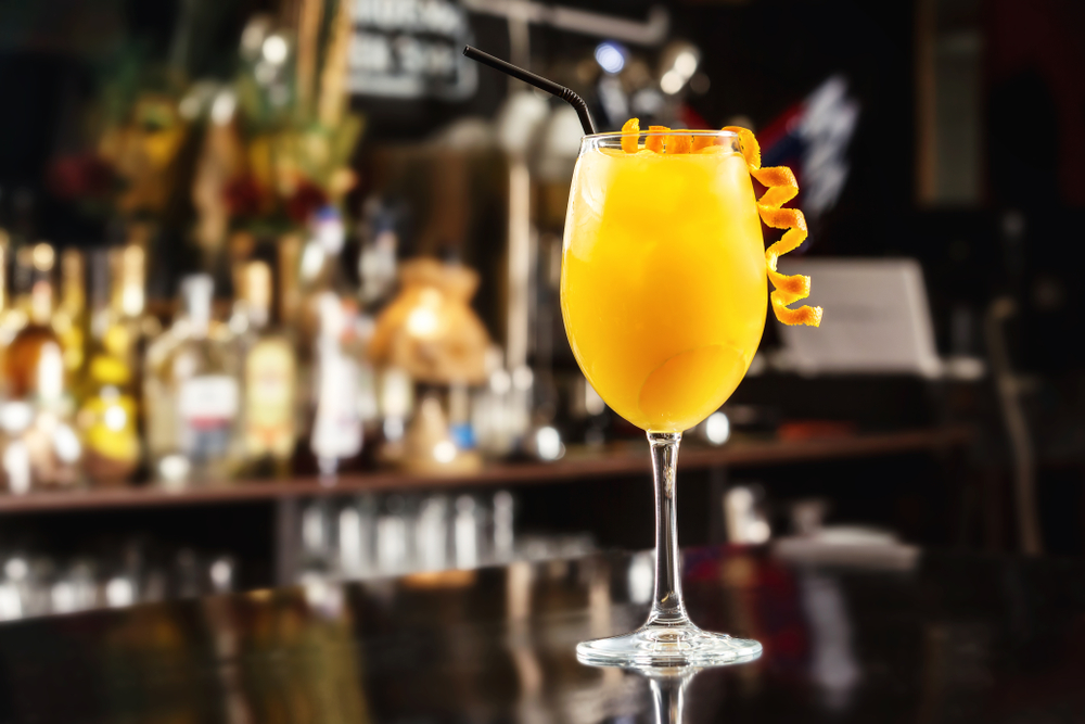 Closeup glass of orange screwdriver cocktail at bar counter background.