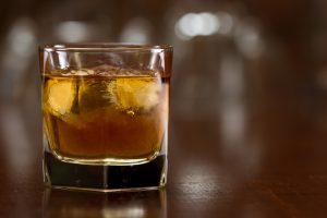 bourbon whiskey served with ice on a out of focus busy bar